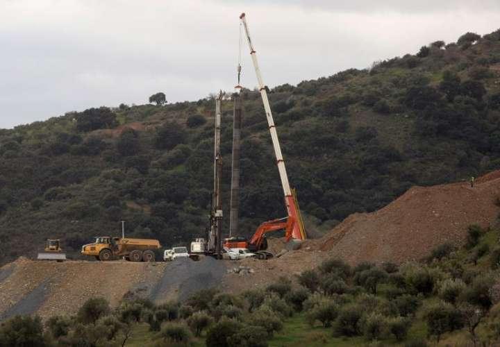 Grúa mantiene suspendido el tubo en el lugar de los trabajos porque un nuevo saliente detectado en los últimos metros del túnel vertical de 60 metros perforado para rescatar niño de 2 años que cayó a un profundo en Totalán (Málaga). EFE
