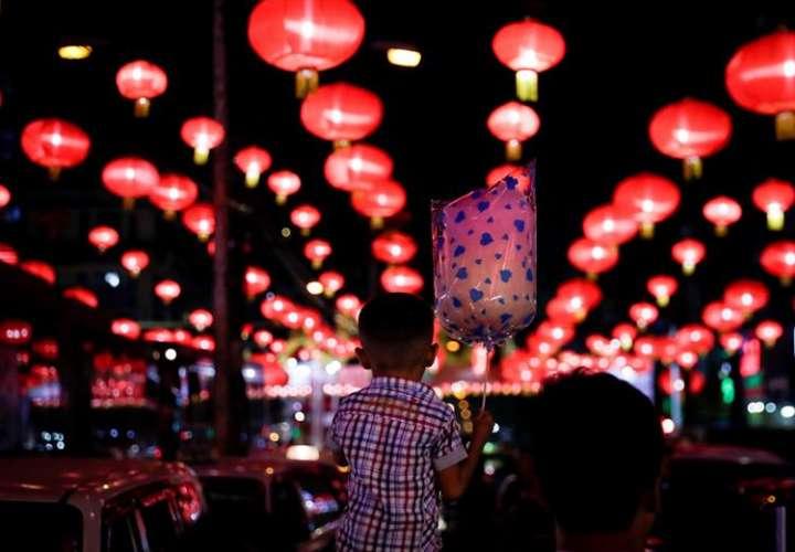 La gente camina bajo la decoración de una puerta de Buda antes de las celebraciones del Año Nuevo Lunar Chino en el templo Dong Zen en Jenjarom, en las afueras de Kuala Lumpur, Malasia. EFE