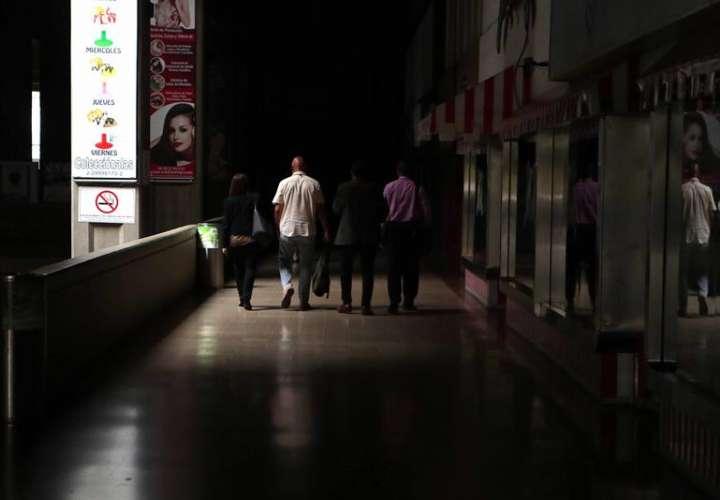 Un grupo de personas camina por un local comercial a oscuras por el apagón eléctrico en Caracas (Venezuela). EFE