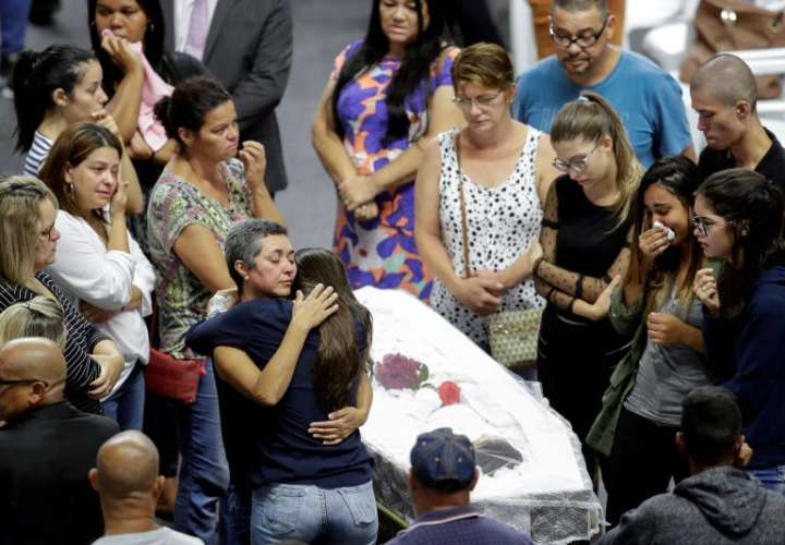 Familiares, amigos y vecinos en el gimnasio municipal donde se celebra el velatorio conjunto de seis de las diez víctimas fatales del tiroteo perpetrado ayer por dos adolescentes en una escuela pública de Suzano, una ciudad del estado de Sao Paulo. EFE
