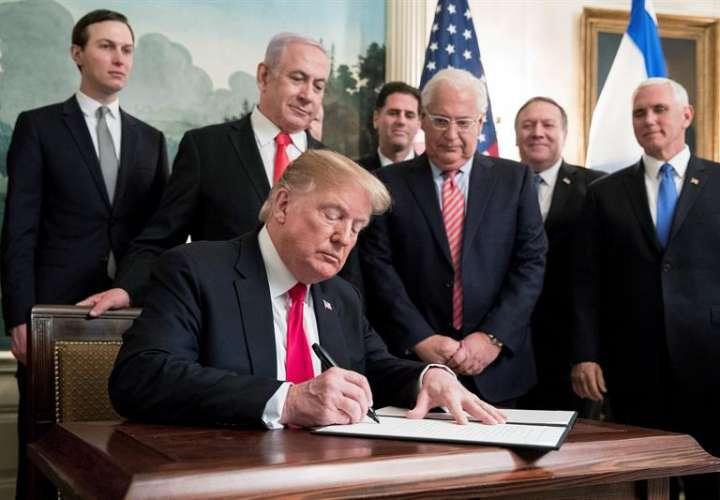 El presidente estadounidense, Donald trump (c), firma un decreto ante la mirada del primer ministro israelí, Benjamin Netanyahu (centro detrás), este lunes en la Casa Blanca, Washington (Estados Unidos). EFE