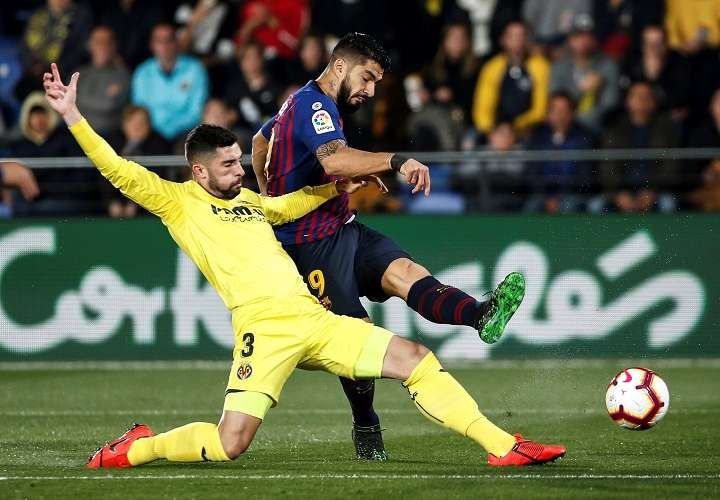 El delantero uruguayo del FC Barcelona Luis Suárez (d), dispara a puerta frente al defensa del Villarreal CF Álvaro González. Foto: EFE