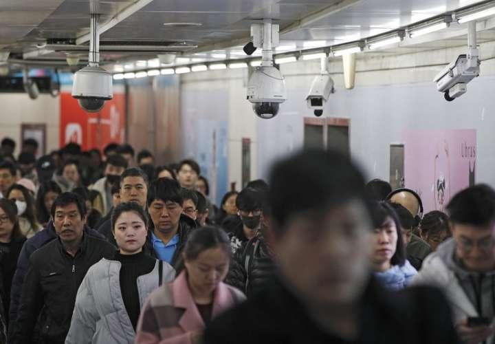 Viajeros caminan junto a las cámaras de vigilancia instaladas en una pasarela entre dos estaciones de metro en Beijing. AP