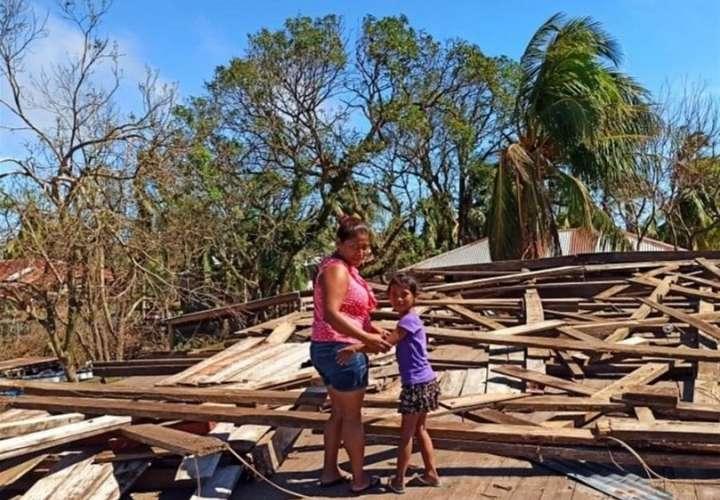 La indígena miskita Hamlyn Ávila Krik, (i), junto a su sobrina (d), observan hoy viernes la vivienda donde habitaban y que fue destruida por el paso del huracán Iota. EFE