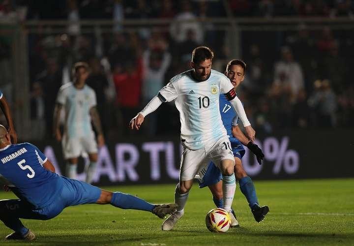 Leonel Messi (c) disputa un balón con Renato Punyed de Nicaragua. Foto: EFE