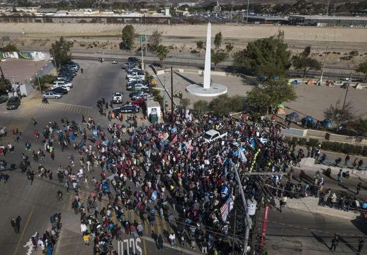 Migrantes se reúnen en el cruce fronterizo Chaparral, entre Tijuana, México y EE.UU. Foto: AP
