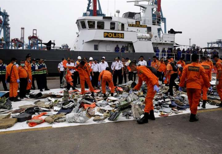 Miembros de los servicios de rescate recuperan restos del avión accidentado en el puerto Tanjung Priok durante las tareas de rescate en el mar de Java cerca de la costa indonesia. EFE