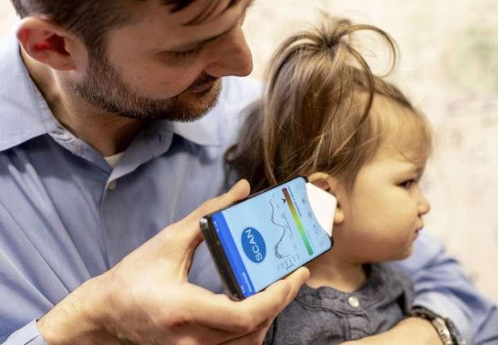 El Dr. Randall Bly usa una aplicación de teléfono y un embudo de papel para enfocar el sonido, para verificar si su hija tiene una infección en el oído, en la Escuela de Medicina de la Universidad de Washington en Seattle. AP