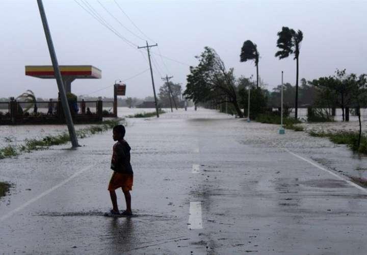 Varias personas caminan bajo la lluvia por una carretera en la localidad de Casiguran (Filipinas) hoy, 30 de octubre de 2018.  EFE