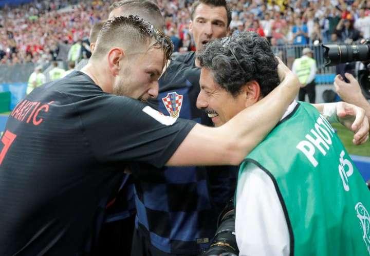 El jugador de Croacia Ivan Rakitic (izq.) se disculpa después de chocar con el fotógrafo Yuri Cortez en la celebración del gol de Mario Mandzukic durante el partido de semifinal del Mundial 2018. Fotos EFE
