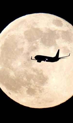 Un avión sobrevuela el cielo con la Luna de fondo. EFE/Archivo