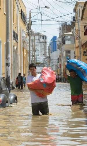 Dos vendedores cargan costales con mercancía por una calle inundada por el río Piura el 27 de marzo de 2017, en Piura (Perú). EFE