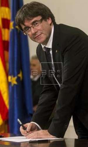El presidente de la Generalitat, Carles Puigdemont, firma el documento después de comparecer ante el pleno del Parlament para trasladar los resultados de la jornada del 1-O. EFE