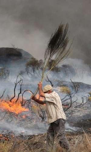 Un hombre trata de sofocar las llamas del incendio desatado la población de Almeidinha, en el distrito de Guarda, cerca de la frontera con la provincia española de Salamanca, donde las llamas llegaron hasta el casco urbano. EFE