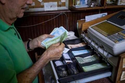 Una persona maneja una caja registradora en un local comercial con moneda venezolana y dólares estadounidenses. EFE