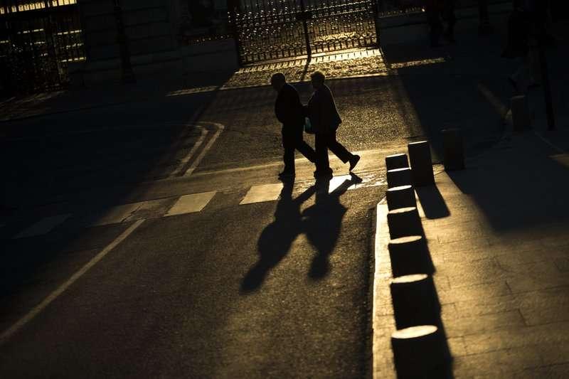 una pareja de ancianos camina por una calle cerca del Palacio Real de Madrid.  AP