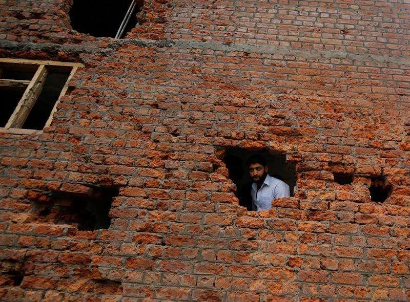 Un hombre se asoma por un agujero en la fachada de una vivienda que resultó dañada durante un tiroteo entre rebeldes y paramilitares indios en Srinagar, capital estival de la Cachemira india. EFE