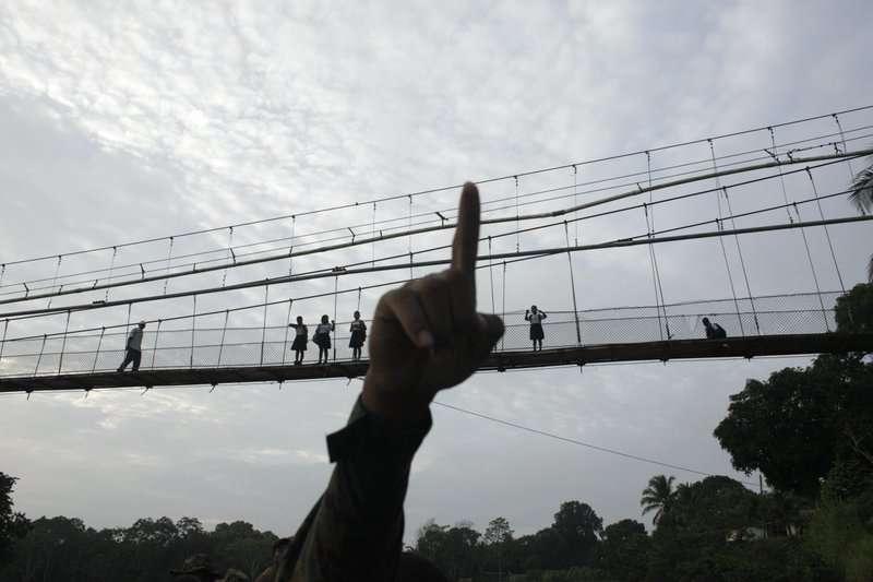En esta foto del 19 de junio de 2018, un policía de fronteras señala mientras empieza a patrullar en la provincia del Darién, frontera con Colombia, en Yaviza, Panamá. (AP Foto/Arnulfo Franco, Archivo)