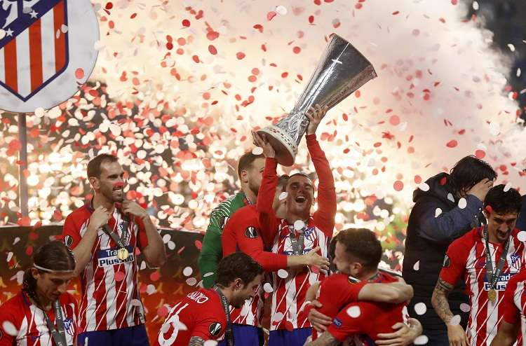 Antoine Griezmann (c) de Atlético Madrid sostiene el trofeo junto a sus compañeros hoy. Foto: EFE