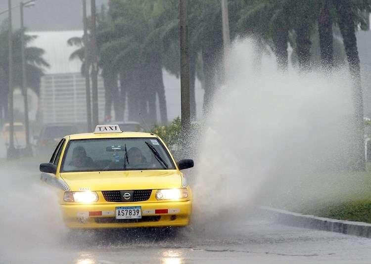 Un vehículo transita por una vía inundada
