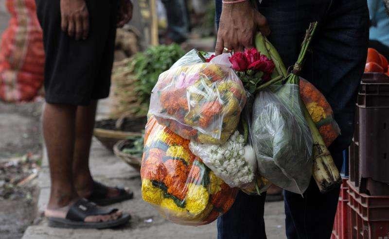 Un hombre porta flores en bolsas de plástico en el mercado de Dadar, en Bombay (India), hoy, 22 de junio de 2018. EFE
