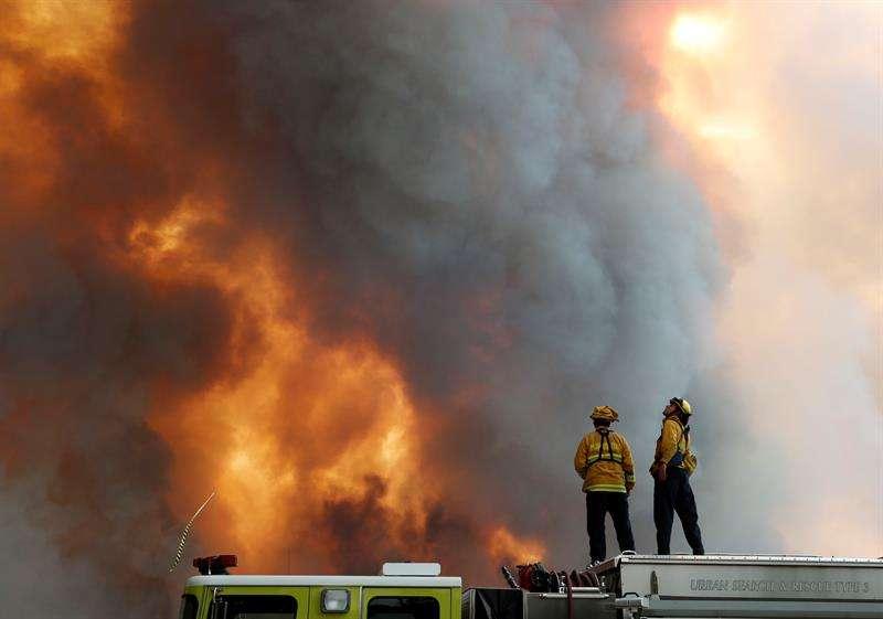 Un par de bomberos fue registrado al observar la ladera de una colina en llamas en Lakeport (California, EE.UU.). EFE