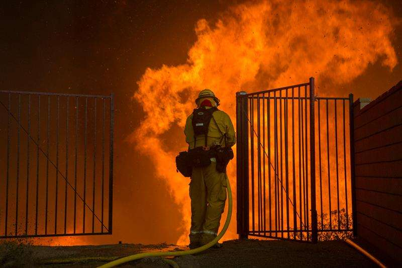 Un bombero trata de apagar un incendio hoy, jueves 9 de agosto de 2018, en Corona, California (EE.UU.). EFE