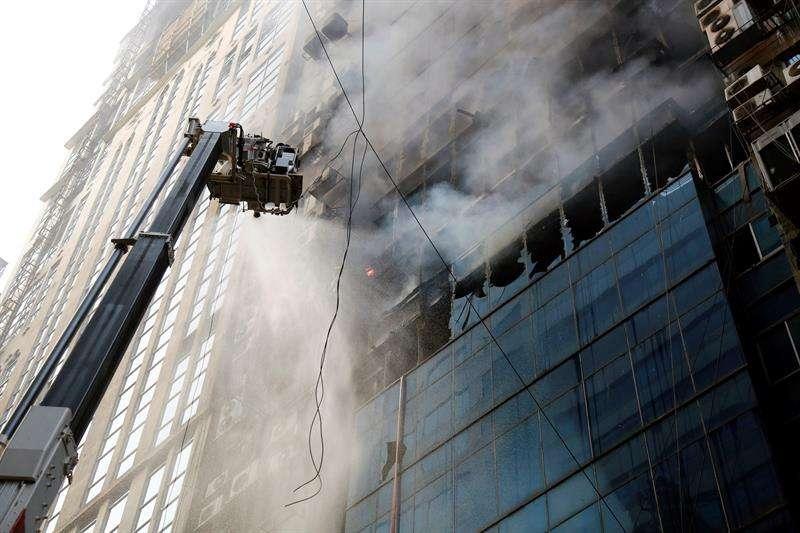 Miembros del cuerpo de bomberos de Bangladesh intentan apagar el incendio que se ha producido en un edificio, este jueves en Dacca (Bangladesh). EFE