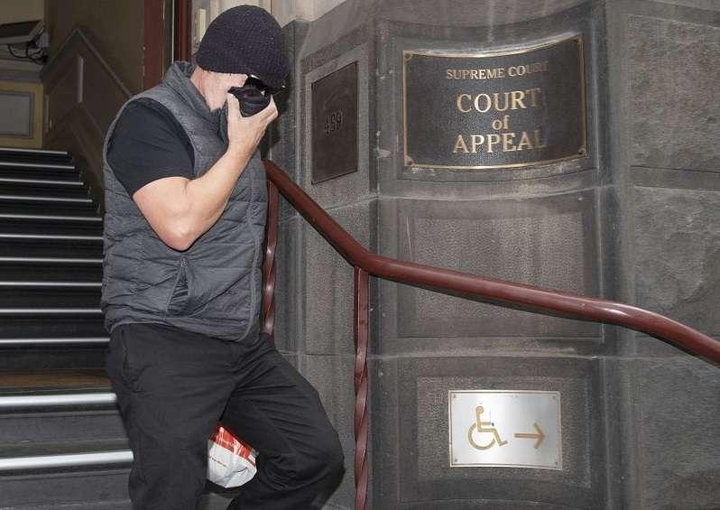 David Hingst, reclamante de acoso en el lugar de trabajo, se cubre la cara cuando abandona el Tribunal de Apelación en Melbourne, Australia, el viernes 29 de marzo de 2019. AP