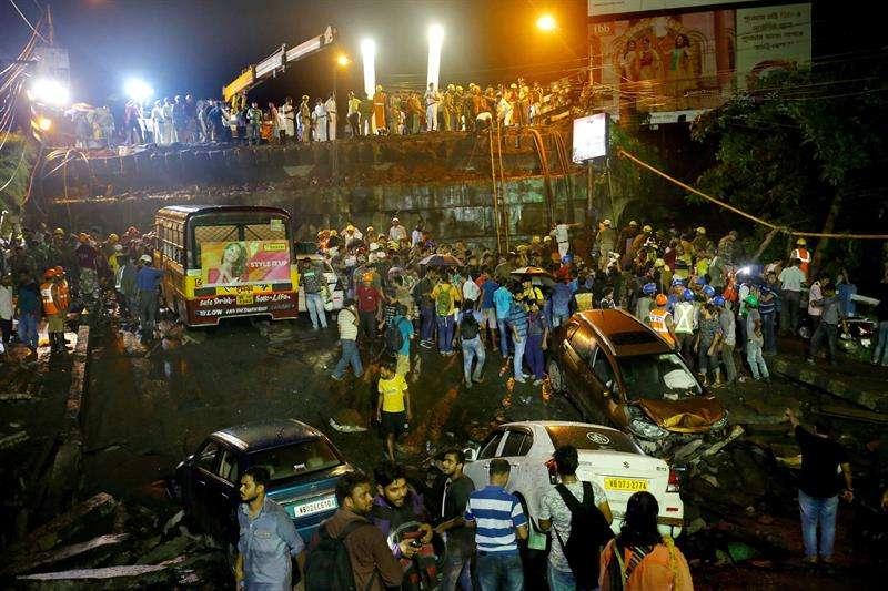 Miembros de fuerzas de rescate y efectivos del ejército indio trabajan en las labores de rescate de posibles víctimas en el lugar en el que un puente se ha derrumbado en Calcuta (India). EFE