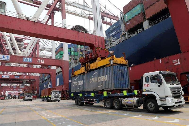 Foto de archivo de un camión mientras descarga un contenedor en el puerto de Qingdao (China). EFEArchivo