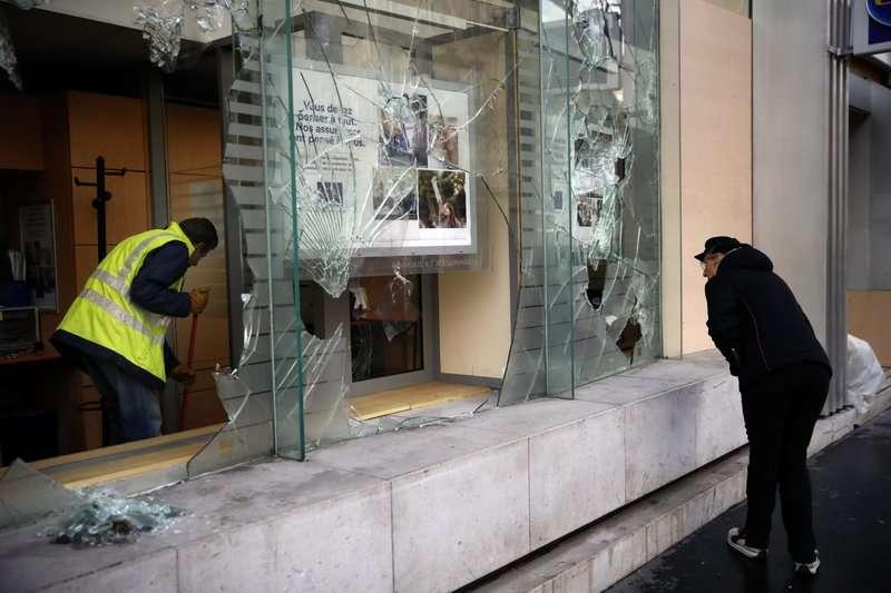 Un trabajador limpia los escombros en un banco mientras un hombre mira a través de las ventanas rotas, en París, el domingo 9 de diciembre de 2018.  AP