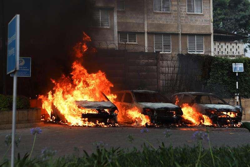 Vista de tres coches en llamas tras una serie de explosiones cerca de un complejo hotelero en Nairobi, Kenia. EFE