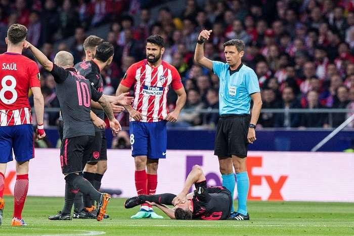 El defensa francés del Arsenal Laurent Koscielny (2d) tras lesionarse en el partido ante del Atlético de Madrid./ EFE