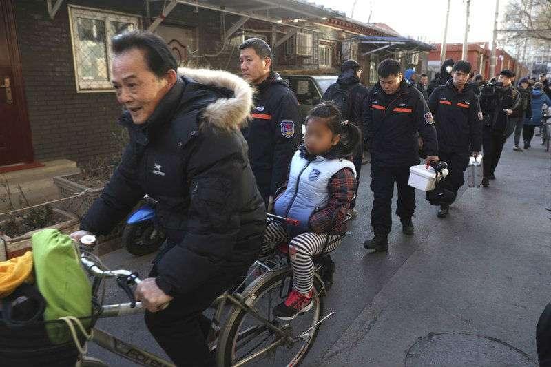 Un hombre lleva una niña en bicicleta junto a los investigadores en el exterior de la escuela elemental número 1 de Beijing en Xuanwu, en Beijing, China. AP