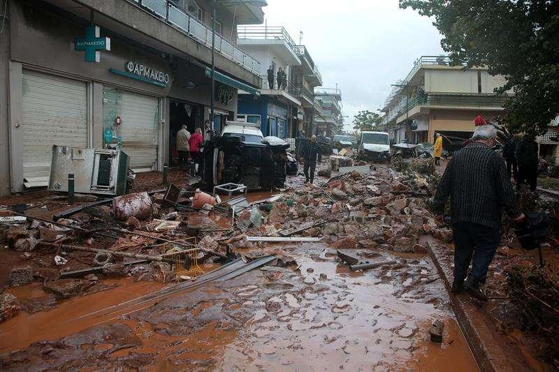 Residentes inspeccionan los destrozos causados por las inundaciones en el centro de Mandra (Grecia).  /  EFE