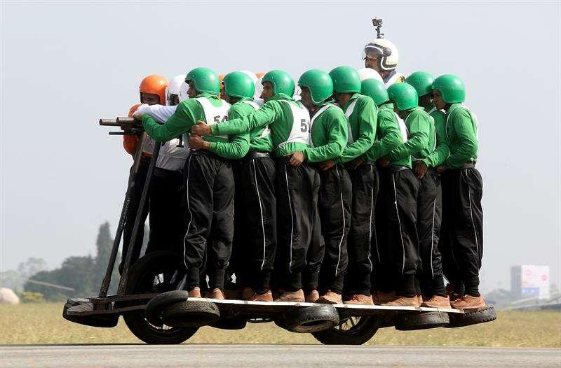Los integrantes del equipo de exhibición de motocicletas del Cuerpo de Servicio del Ejército (TAC) se atornillan mientras intentan romper un récord mundial en la Estación de la Fuerza Aérea Yelahanka, en Bangalore. EFE