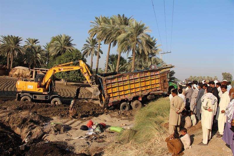 Varias personas observan el camión accidentado en Khairpur, Pakistán. / EFE