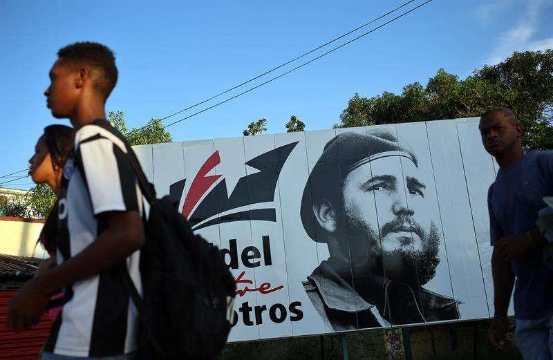 Varias personas caminan frente a un cartel con la imagen de Fidel Castro. / EFE