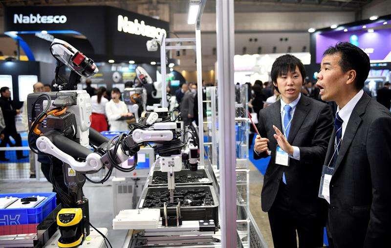 Un par de asistentes observan un robot industrial en el stand de THK en la Feria Internacional de la Robótica en Tokio (Japón) hoy, 29 de noviembre de 2017. Más de 600 compañías y organizaciones presentarán sus novedades hasta el 2 de diciembre. EFE