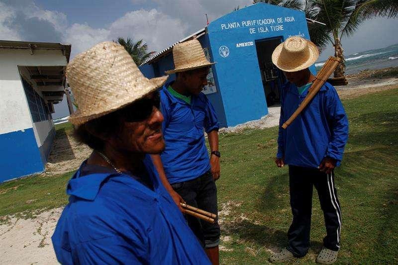 Un grupo de residentes indígenas de Isla Tigre de la Comarca de Guna Yala se reúnen frente a la planta de purificación de agua instalada por la Organización de las Naciones Unidas para la Alimentación y la Agricultura (FAO), en Isla Tigre (Panamá). EFE