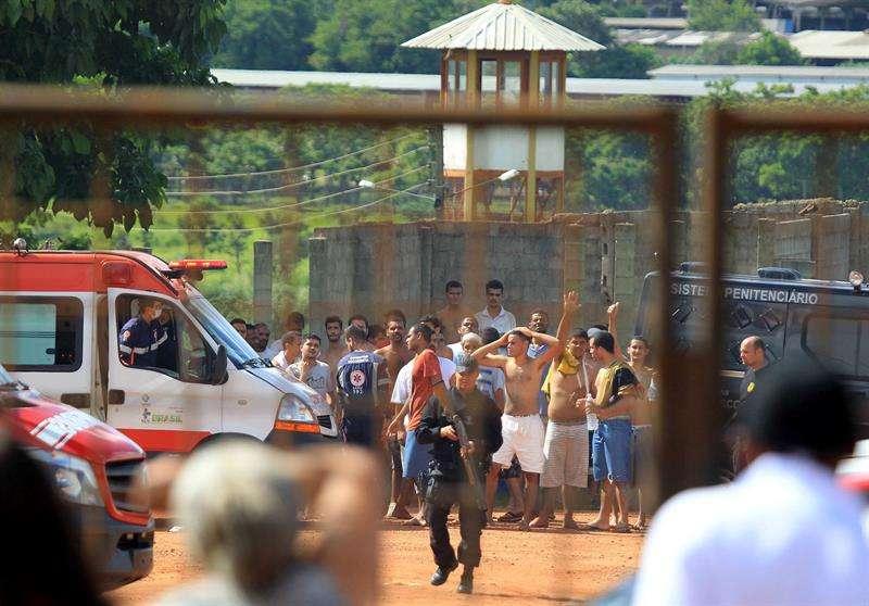 Fotografía cedida de un grupo de presos vigilados por las autoridades el pasado lunes en una cárcel de la región metropolitana de Goiania, capital del estado brasileño de Goiás (Brasil), en la que al menos 9 personas murieron durante un motín. EFE