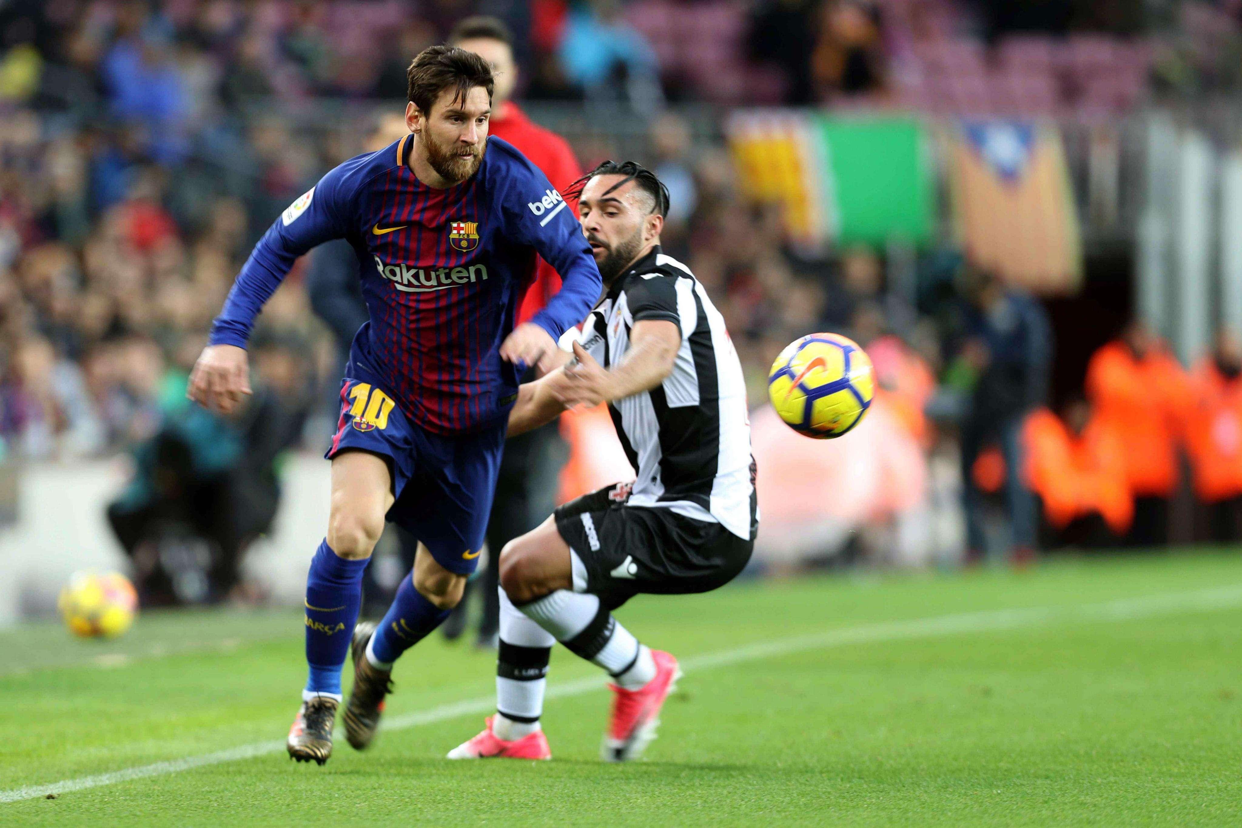 Messi (izq.), intenta escaparse del delantero español del Levante, Ivi López. Foto: EFE