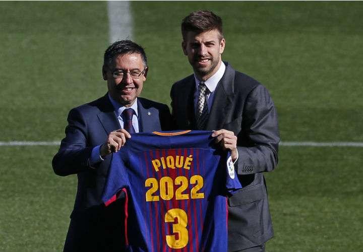 Gerard Piqué (dcha.) posa con el presidente del FC Barcelona, Josep María Bartomeu, durante la renovación de su contrato con el club azulgrana. Foto AP