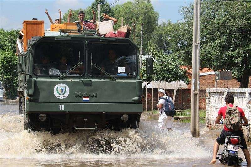 Un vehículo militar transporta familias hoy, martes 30 de enero de 2018, en un barrio de Asunción (Paraguay). EFE