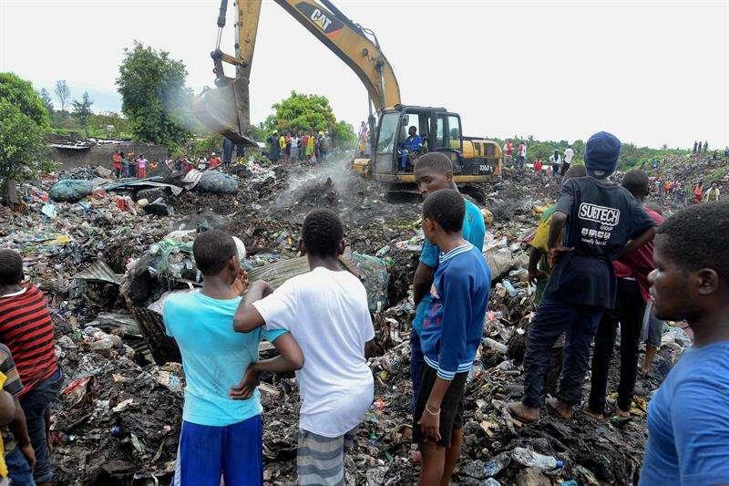 Varias personas observan las labores de búsqueda de los servicios de emergencia en un basurero de Maputo (Mozambique) este 19 de febrero. EFE