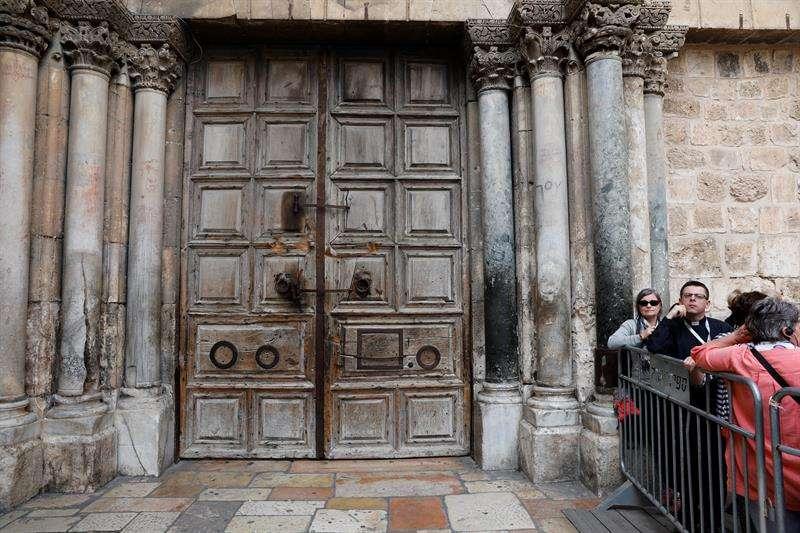 Visitantes esperan a la entrada del Santo Seuplcro, cerrando desde hoy en Jerusalén. EFE