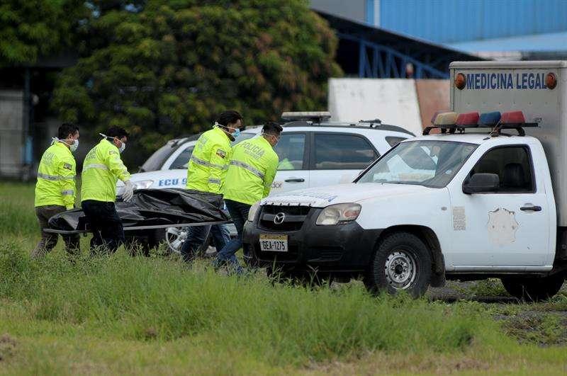 Policías ecuatorianos realizan el levantamiento del cadáver de una de las dos personas que fallecieron al caer presuntamente desde el tren de aterrizaje de un avión. EFE