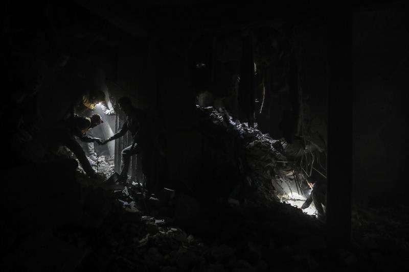 Voluntarios de los Cascos Blancos y civiles buscan supervivientes entre los escombros de un edificio bombardeado esta semana en la rebelde Duma, Guta Oriental (Siria). EFE