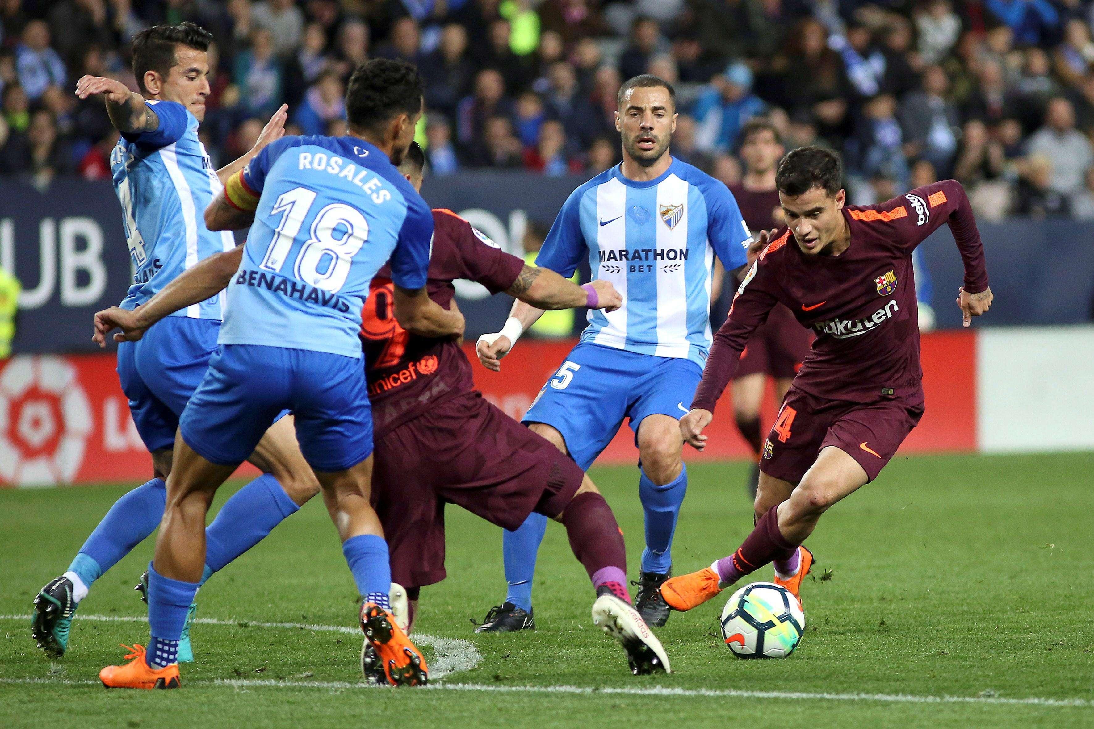 El delantero brasileño del Barcelona Philippe Coutinho (d) se lleva el balón ante varios rivales del Málaga. EFE/Daniel Pérez